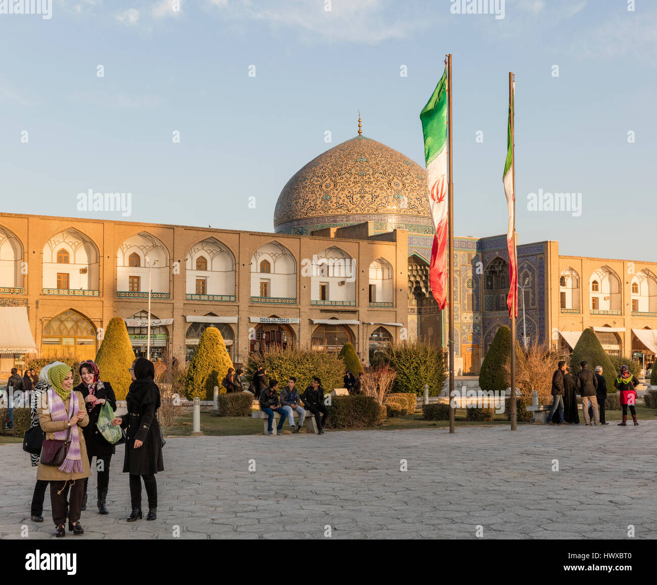 Imam Square in Isfahan with visitors, including families, chador-clad women, and dome of Sheikh Lotfallah Mosque - Stock Image