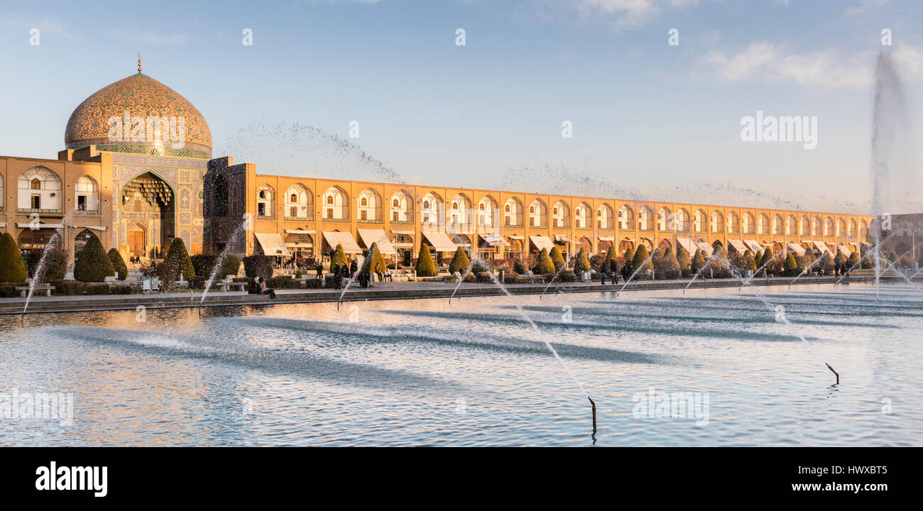 Imam Square in Isfahan with visitors,decorative fountains, and dome of Sheikh Lotfallah Mosque - Stock Image