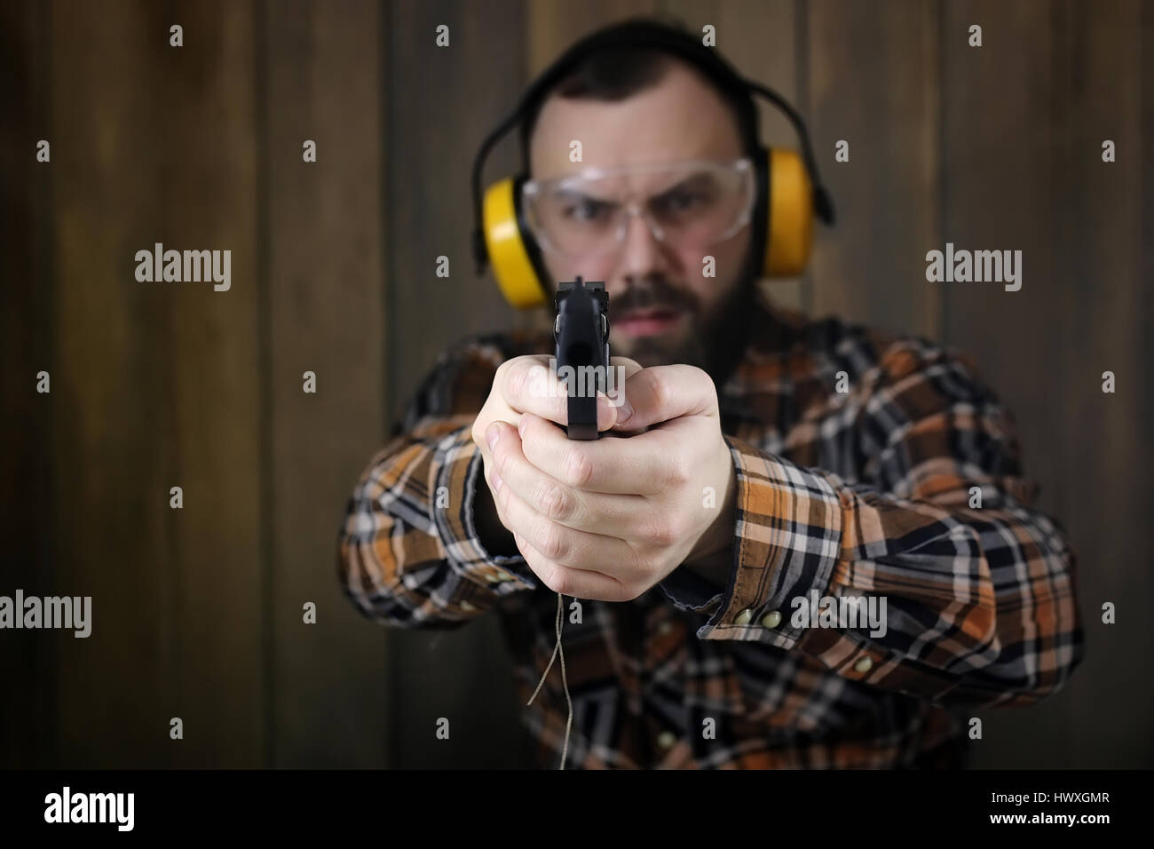 man with put on protective goggles and ear training in pistol sh - Stock Image