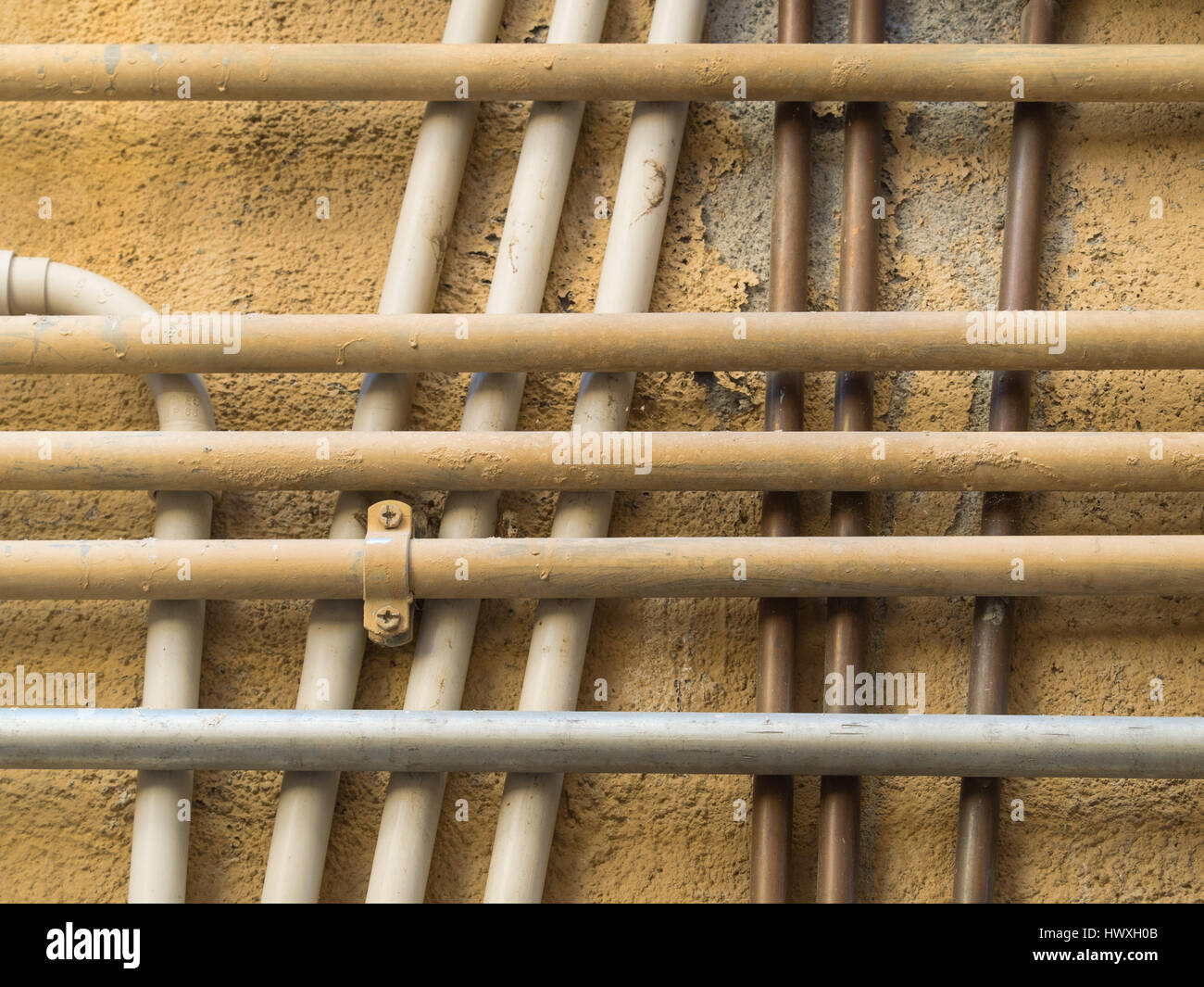 geometric pattern of a group of crossing and overlapping water pipes  on a plastered ocher wall - Stock Image