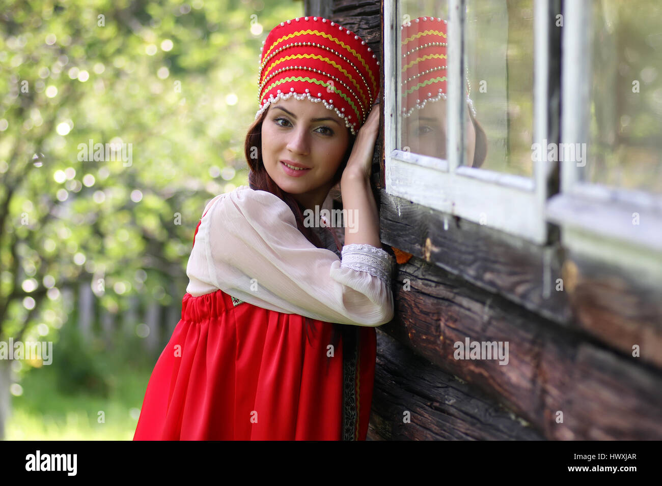 Slav woman in traditional dress wooden wall - Stock Image