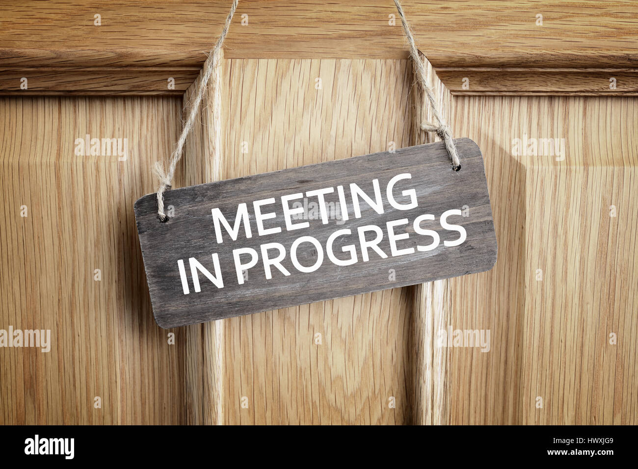 meeting in progress sign on office door concept for business team
