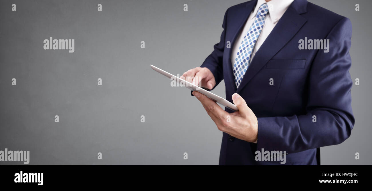 Businessman with tablet computer and gray background for copy - Stock Image