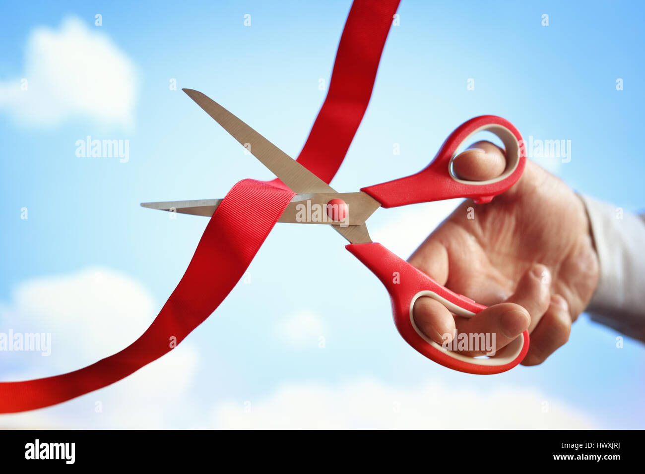 Businessman cutting a red ribbon with a pair of scissors at opening ceremony - Stock Image