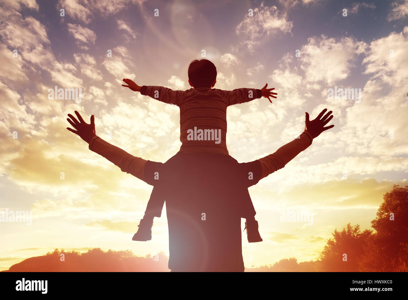 Family time father and son watch and praise the sunset - Stock Image