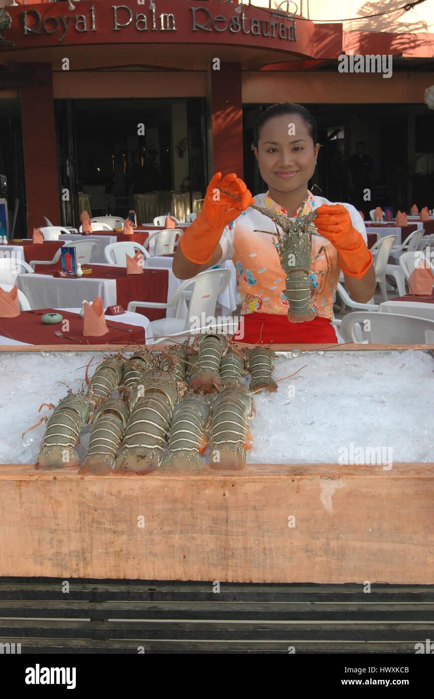 A Waitress showing an optional menu item, Phuket, Thailand - Stock Image