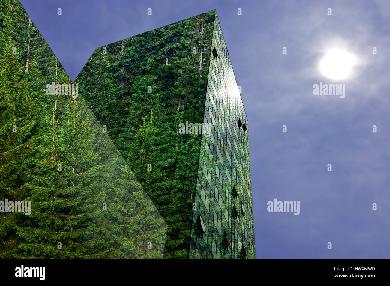 Green, renewable energy in the city: modern building covered with spruce forest. Sustainable energy, pollution and - Stock Image