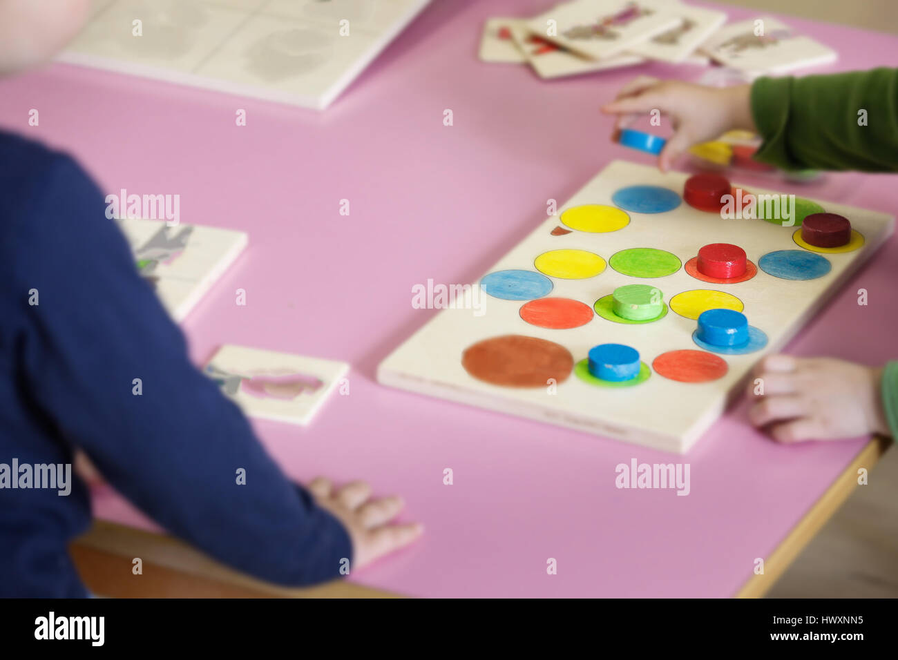 Children playing with homemade, do-it-yourself educational toys, arranging and sorting colors and sizes. Learning - Stock Image