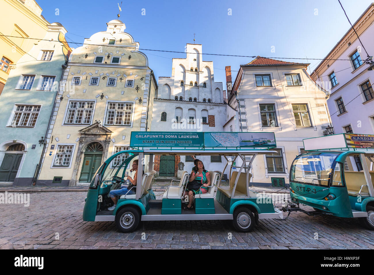 sightseeing tourist train in front of Residential buildings called Three Brothers on the Maza Pils Street on the - Stock Image