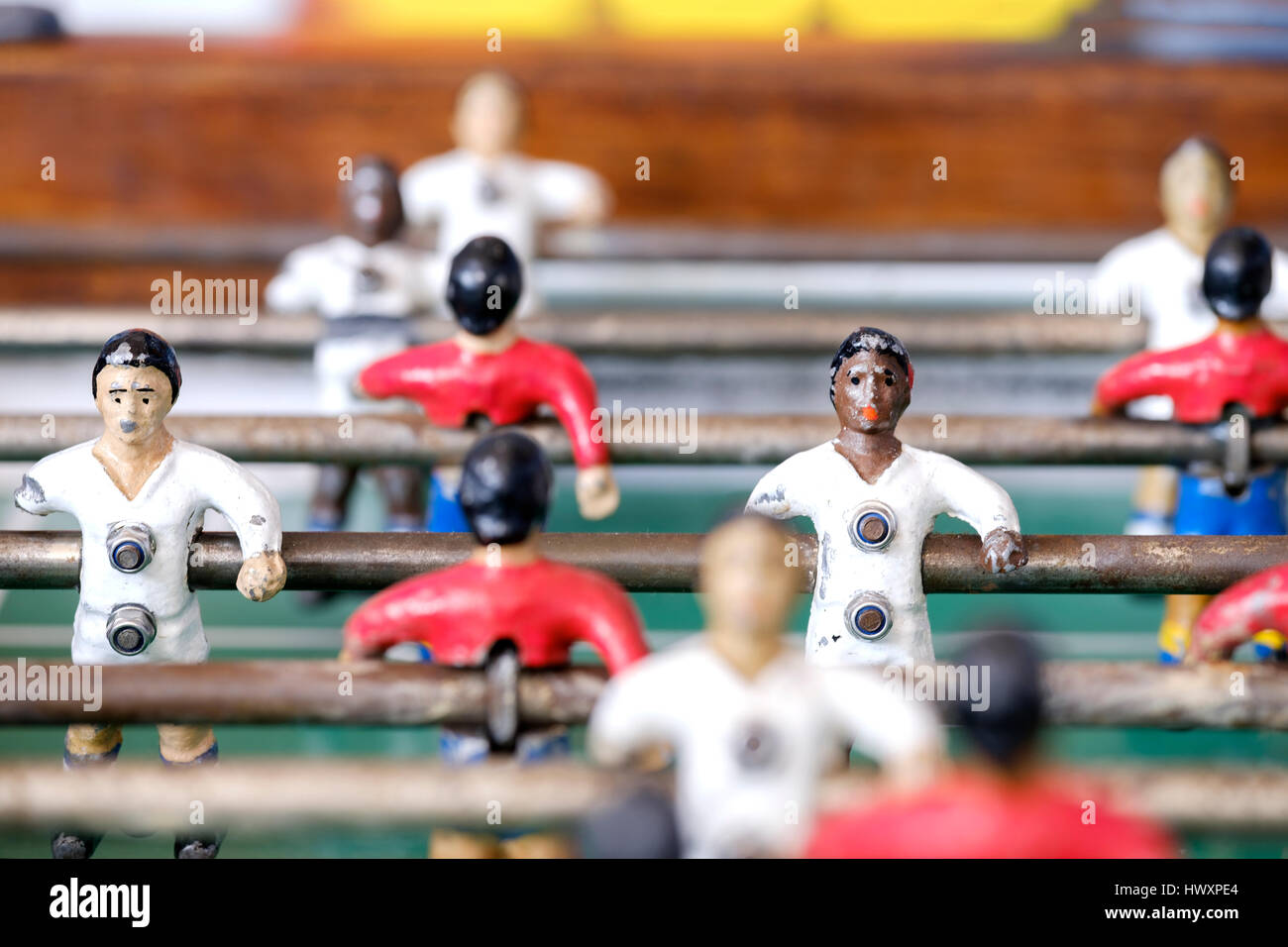 An old fussball, foosball or table football game which has painted shite and black players in red and white football - Stock Image