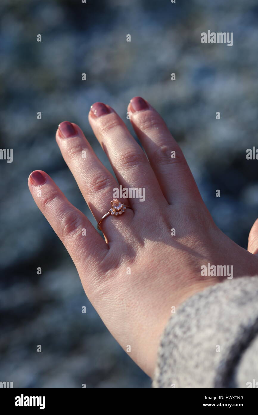 Rose Gold engagement ring on a lady\'s hand with pink painted nails ...