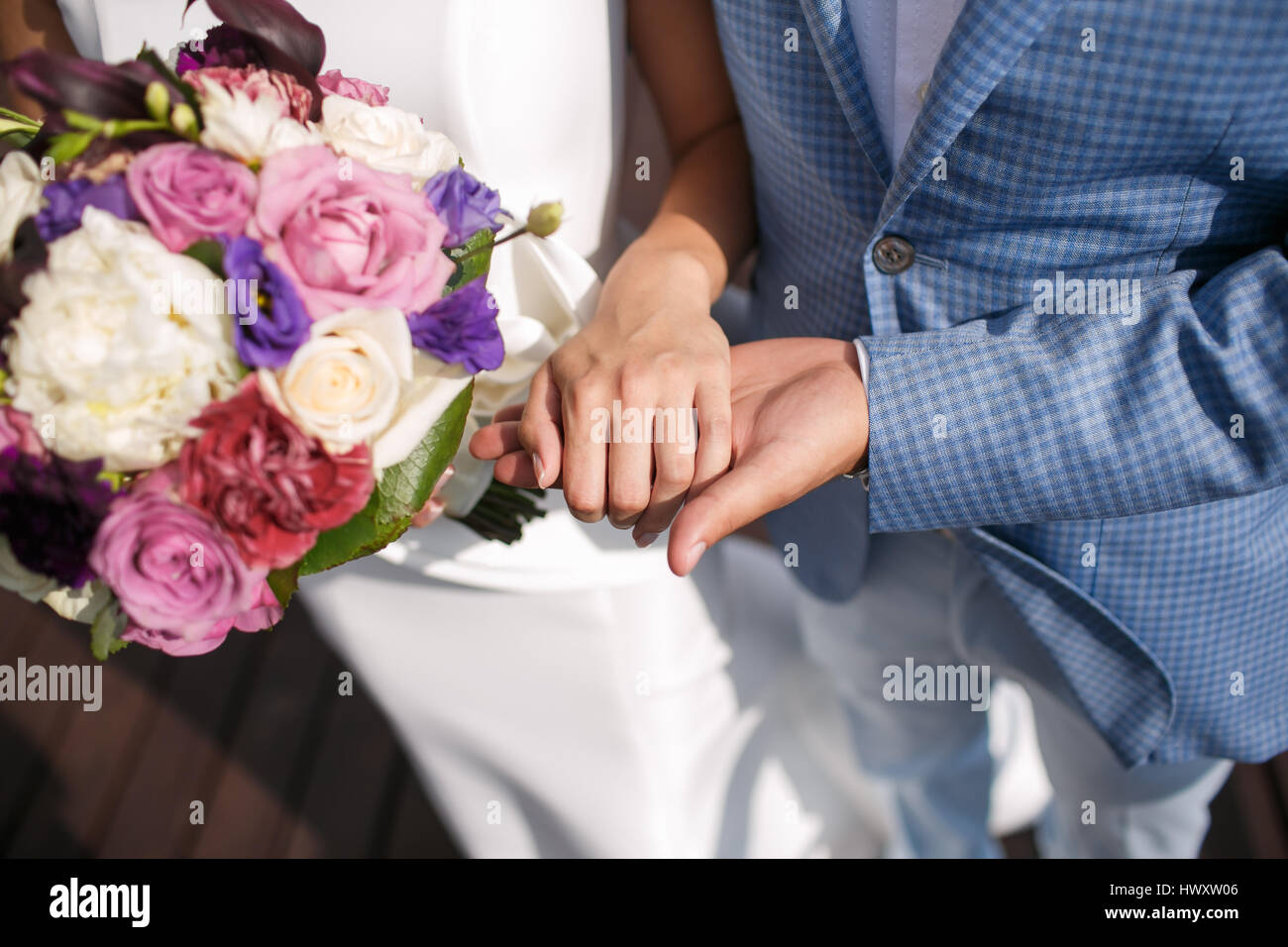 The man the groom keeps the girl's hand. Colorful bridal bouquet. wedding day, bride accessories - Stock Image
