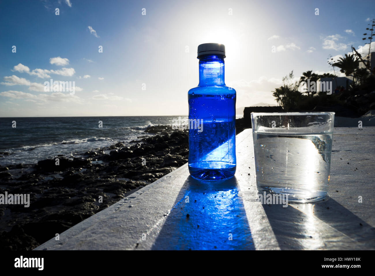 glas and bottle of mineral water at seaside location on Lanzarote - Stock Image