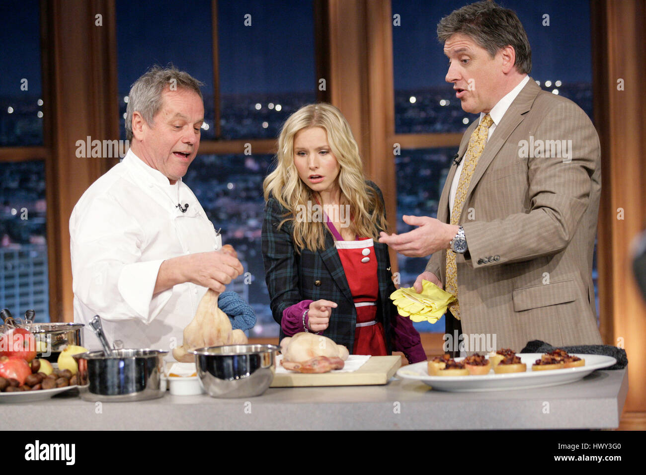 Chef Wolfgang Puck, left, holds a duck head, as actress