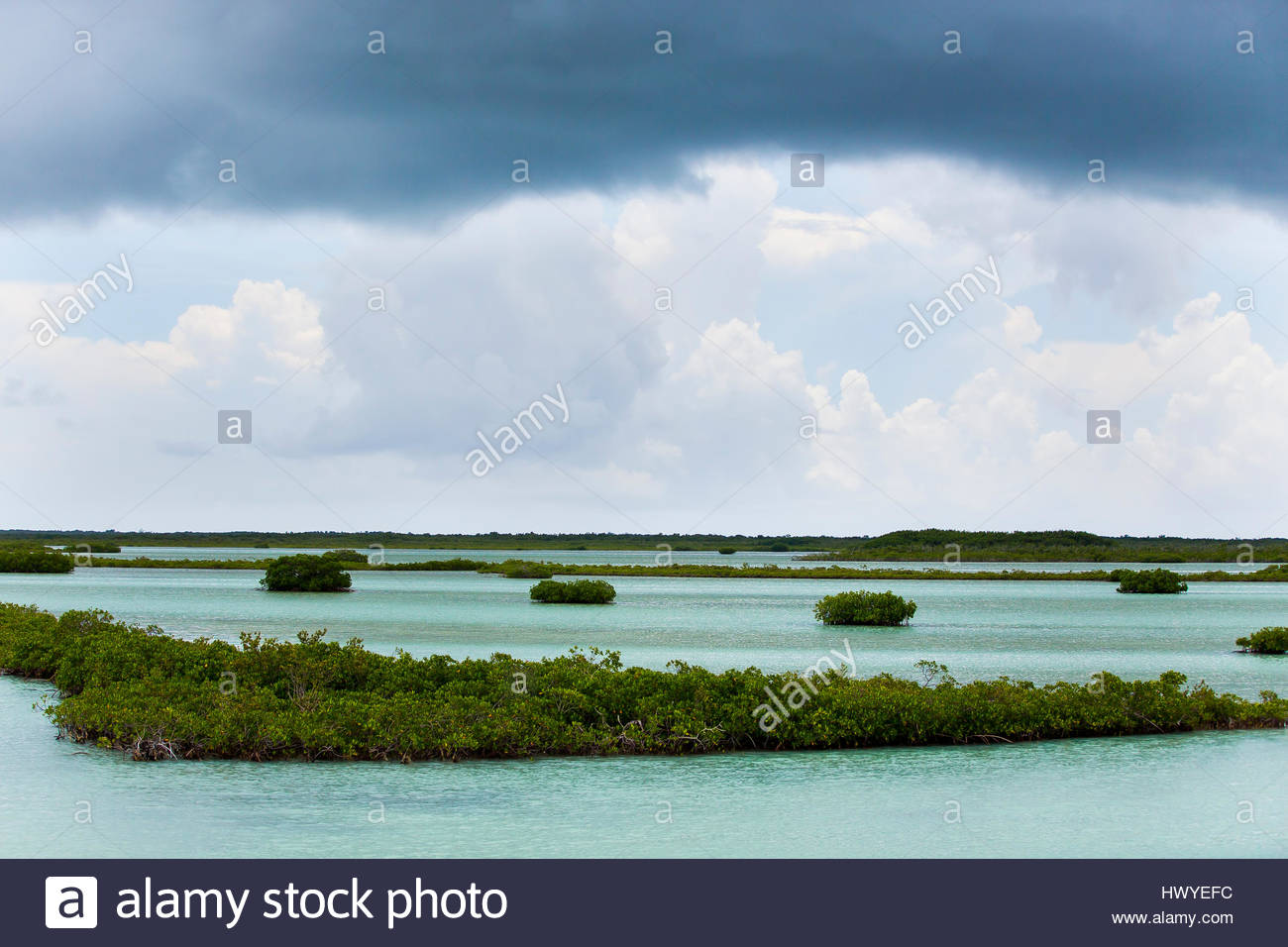 Dark cumulus cloud lines hover above small islands. - Stock Image