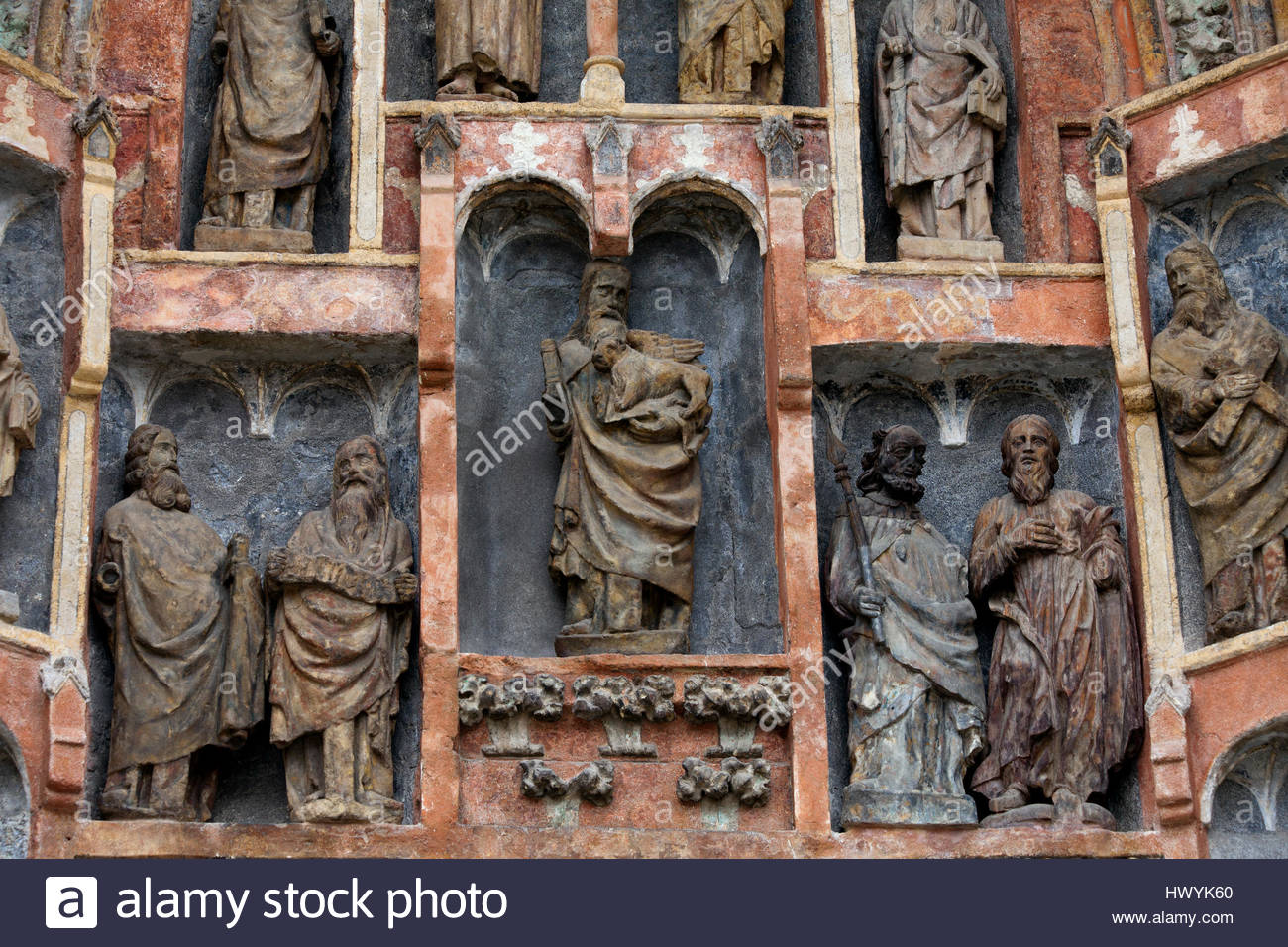 Religious sculptures stand in specific alcoves on a church facade. - Stock Image