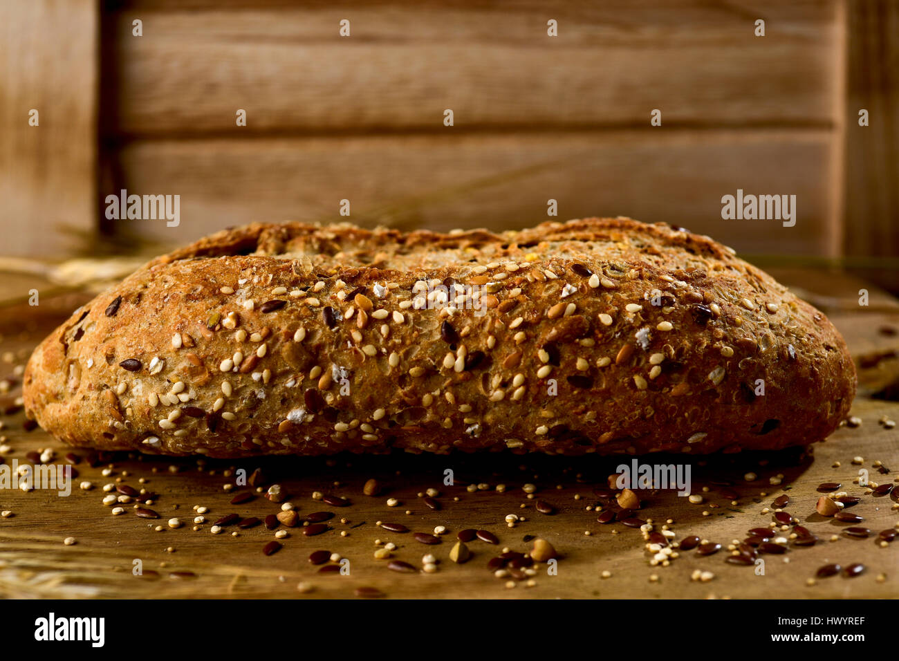 closeup of a wholemeal bread roll topped with different seeds, such as sesame and poppy seeds, on a rustic wooden - Stock Image