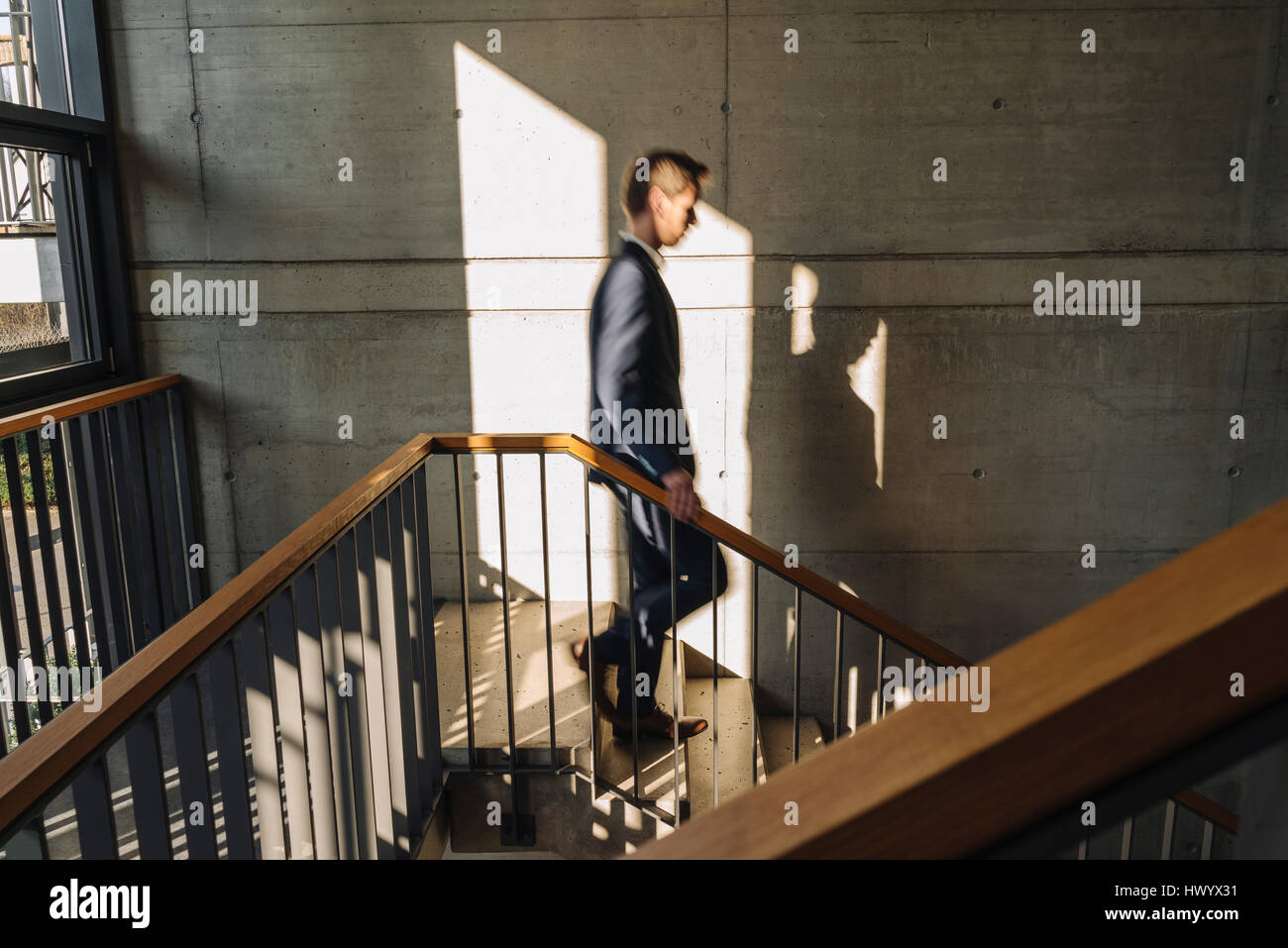 Businessman walking down stairs - Stock Image