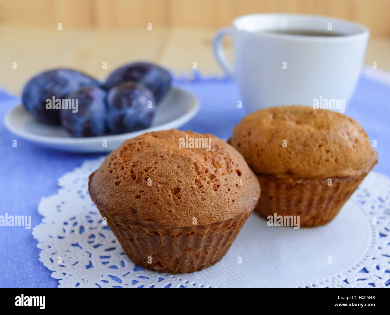 Holiday cupcakes muffins with plums on a wooden background and a cup of tea. - Stock Image