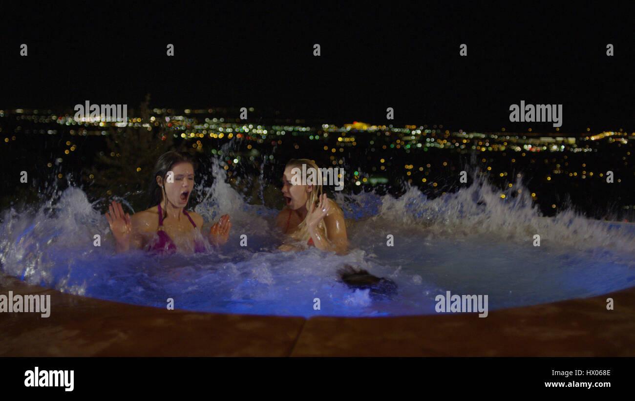 Women splashing in illuminated jacuzzi hot tub overlooking cityscape at night - Stock Image