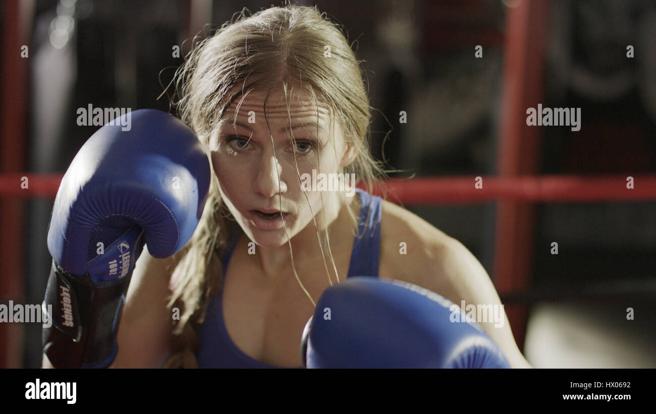 Close up of female boxer in boxing gloves standing in boxing ring during match Stock Photo
