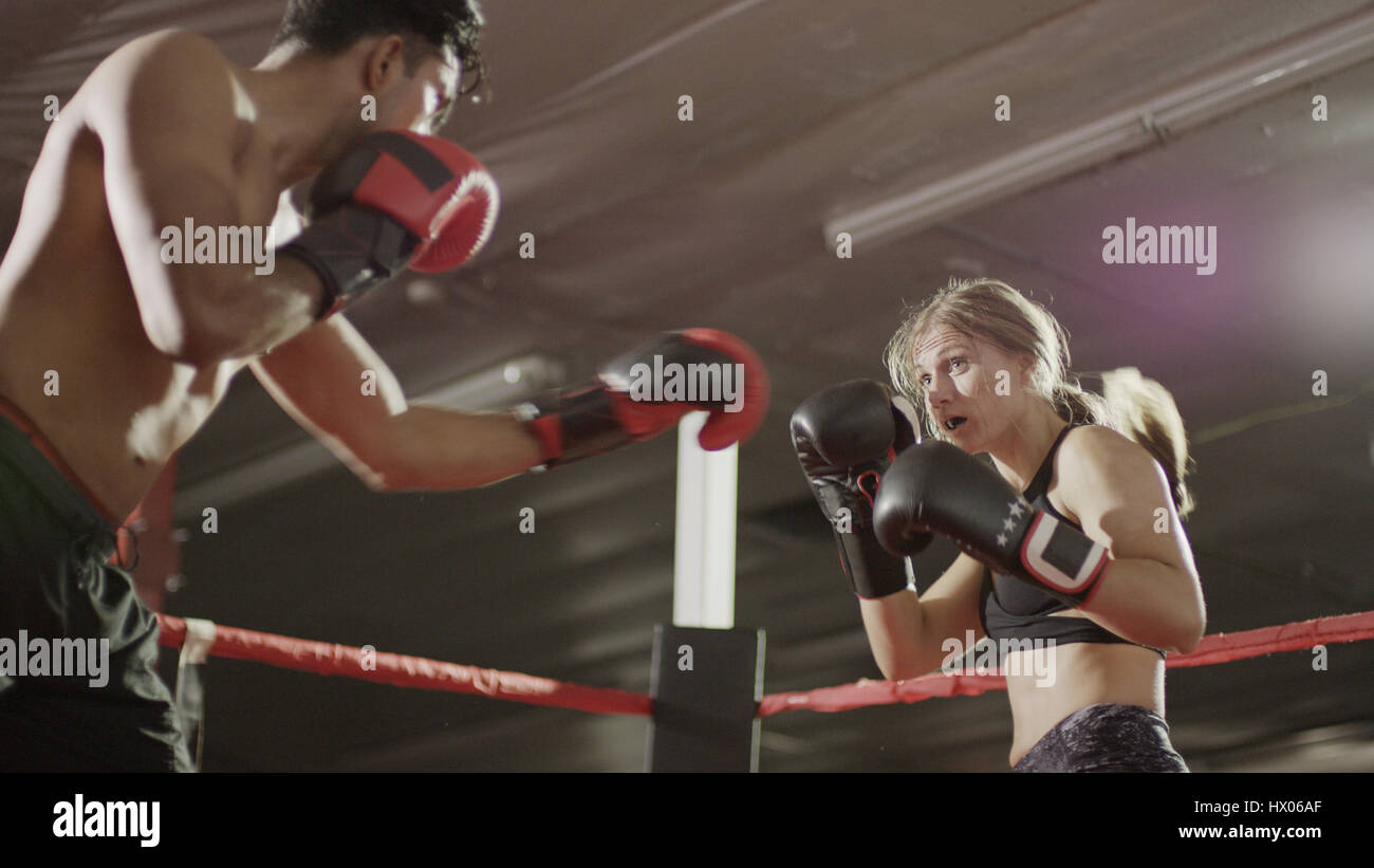 Close up of female boxer protecting her face standing in boxing ring during match Stock Photo
