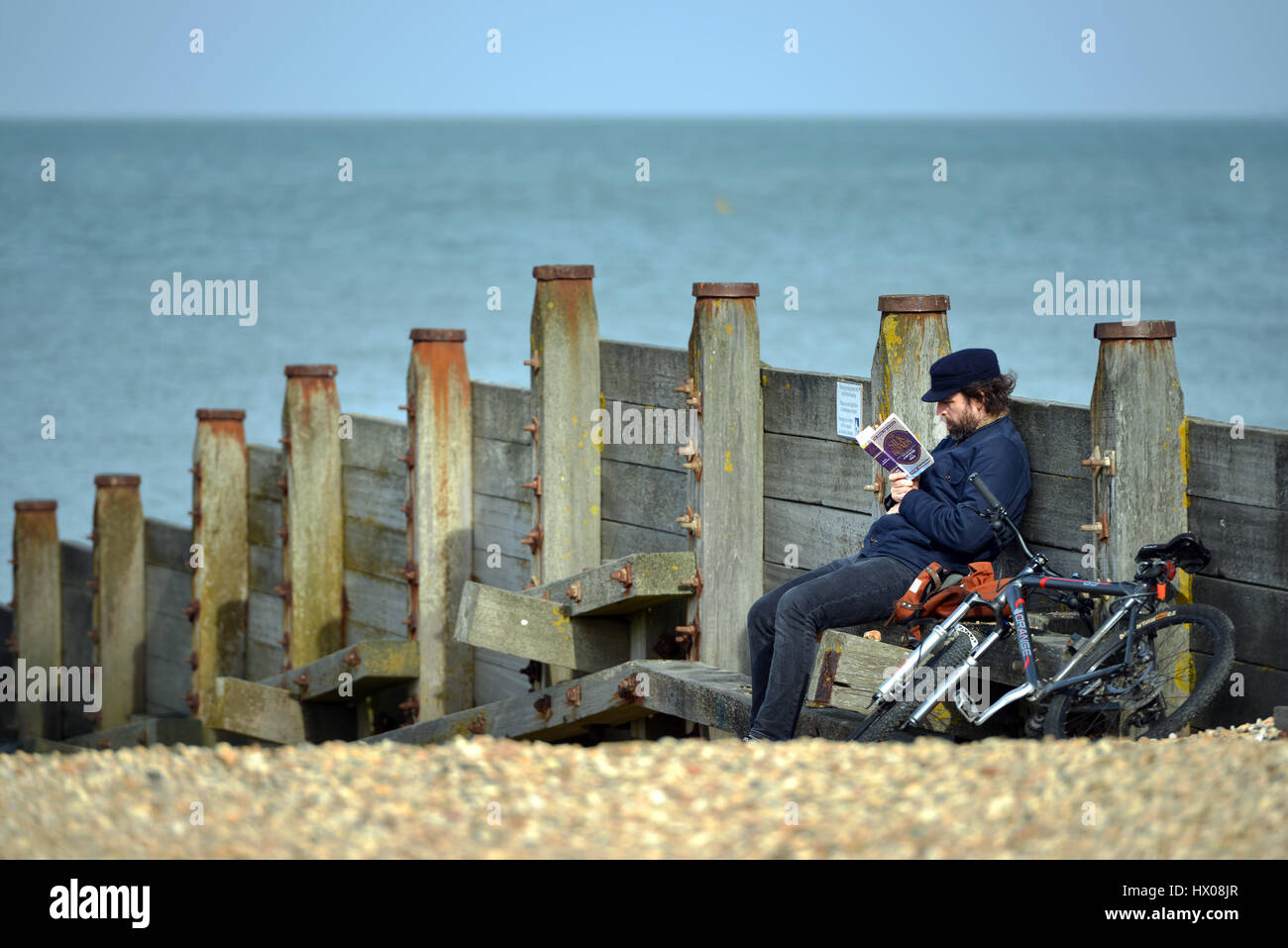 Man with a bike reading a book, Peter Frankopan's The Silk Roads, on a shingle beach, Whitstable, Kent - Stock Image
