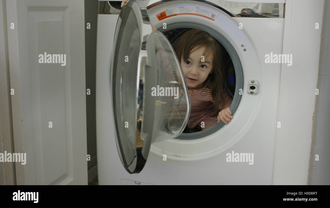 Selective focus close up of exploring playful girl hiding in washing machine - Stock Image