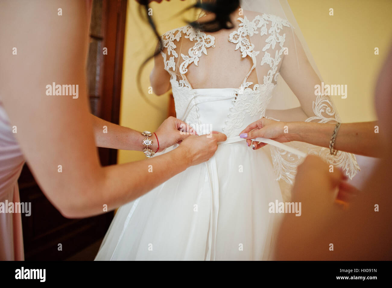 58fb1015a97e Fashionable bridesmaids on pink dresses helped wear bow on back of wedding  dress bride. Morning wedding day.