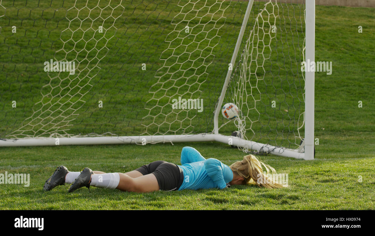 Goalie protecting goal and laying on soccer field during game - Stock Image