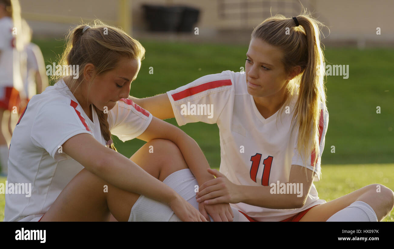 Serious soccer athlete comforting teammate after losing game outdoors - Stock Image