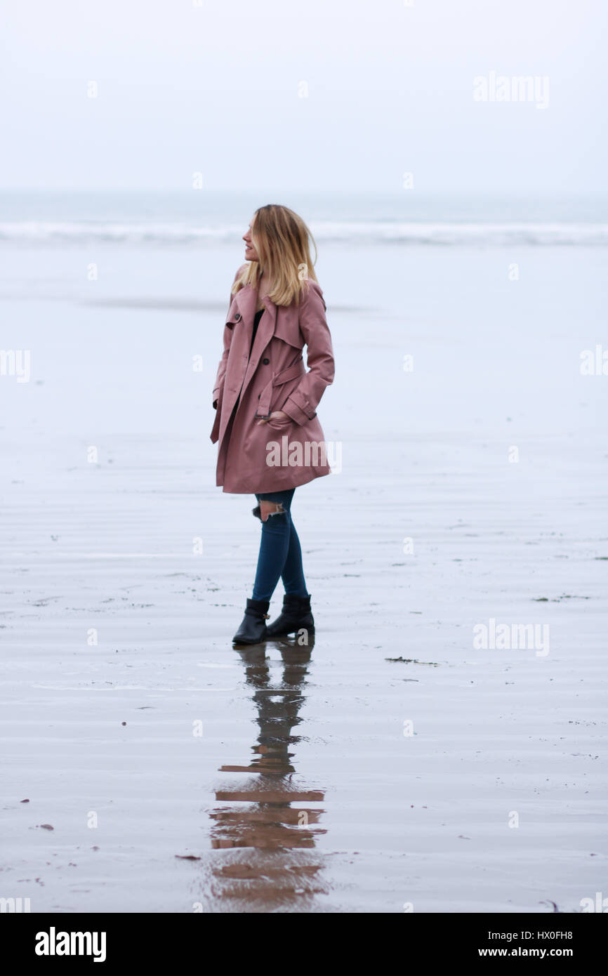 Young blonde woman wearing pink coat on Black Rock Sands Beach - Stock Image