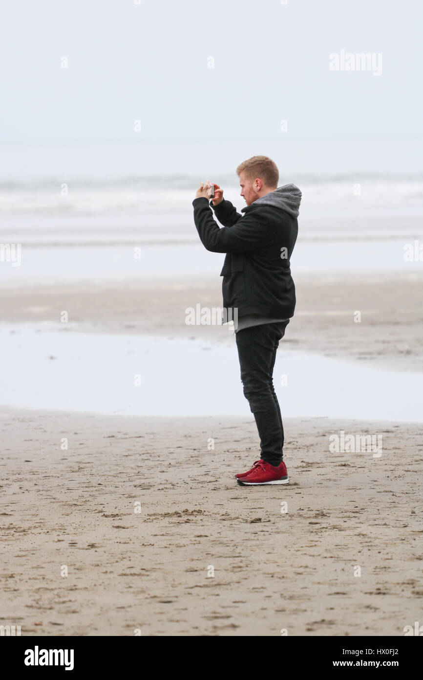 Young man taking photograph on his iPhone on Black rock sands beach - Stock Image