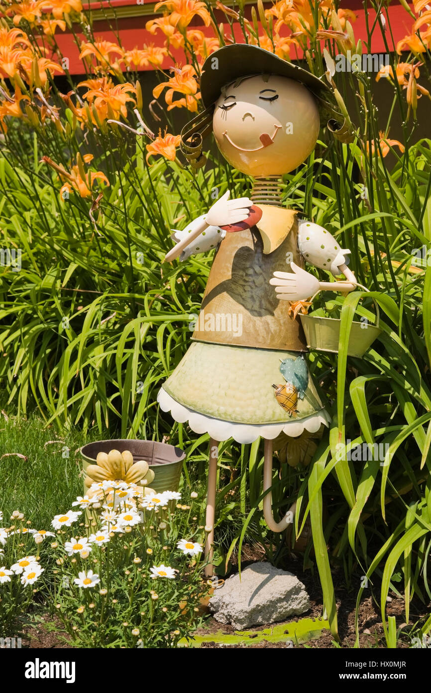 Close-up of metal garden gnome  in front yard garden in summer. - Stock Image