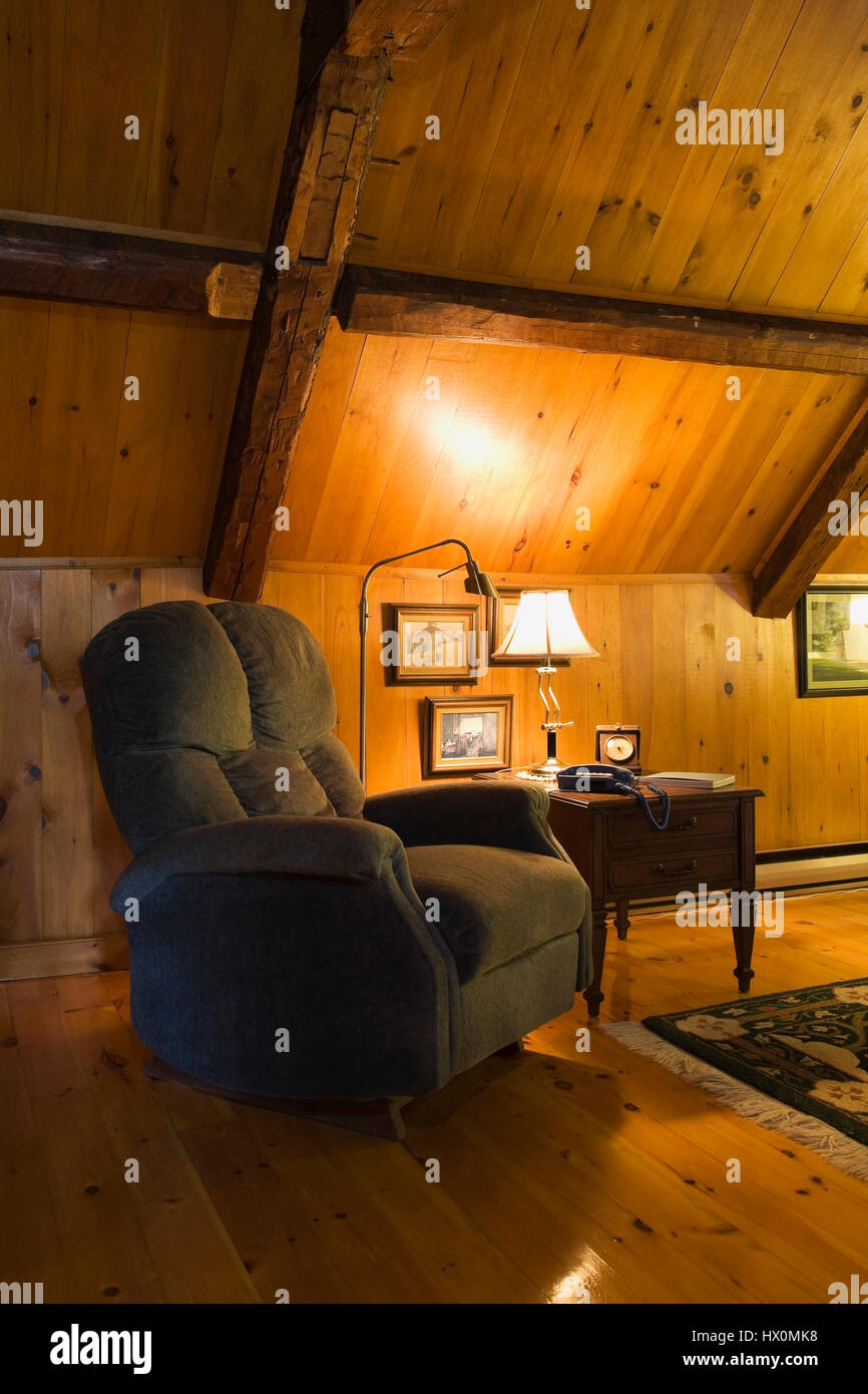 Green upholstered armchair in attic room of 1740 old house interior. - Stock Image