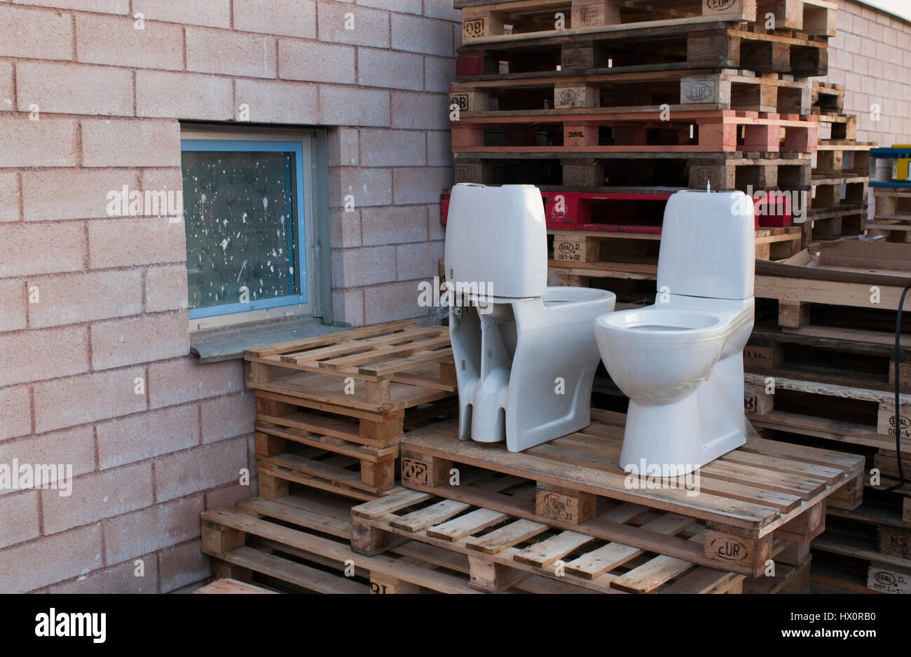 Two toilets including pallets, Upplands Väsby, Sweden. - Stock Image