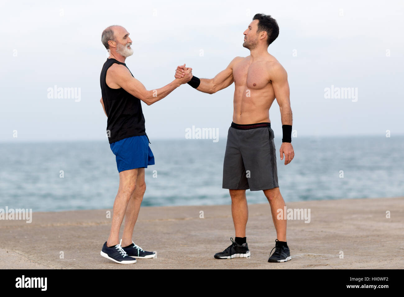 Personal coach on the beach with senior - Stock Image