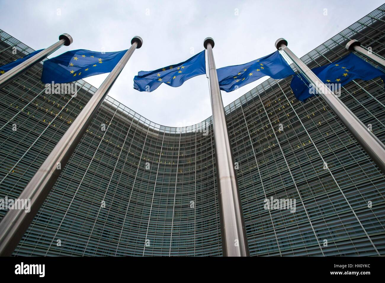 EU flags wave next to the Berlaymont building, headquarters of the European Commission in Brussels, Belgium - Stock Image