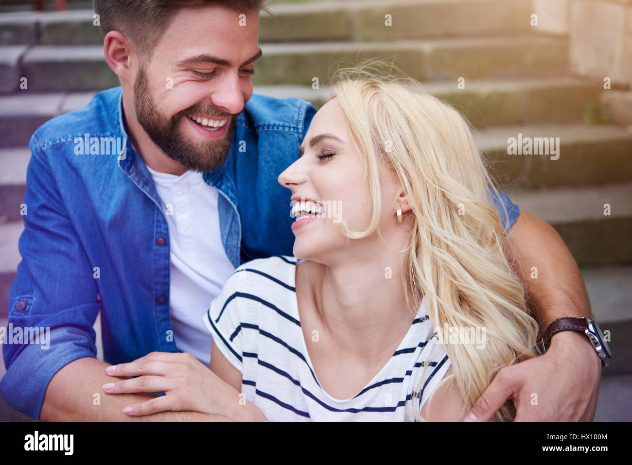 Couple laughing loudly on the steps - Stock Image
