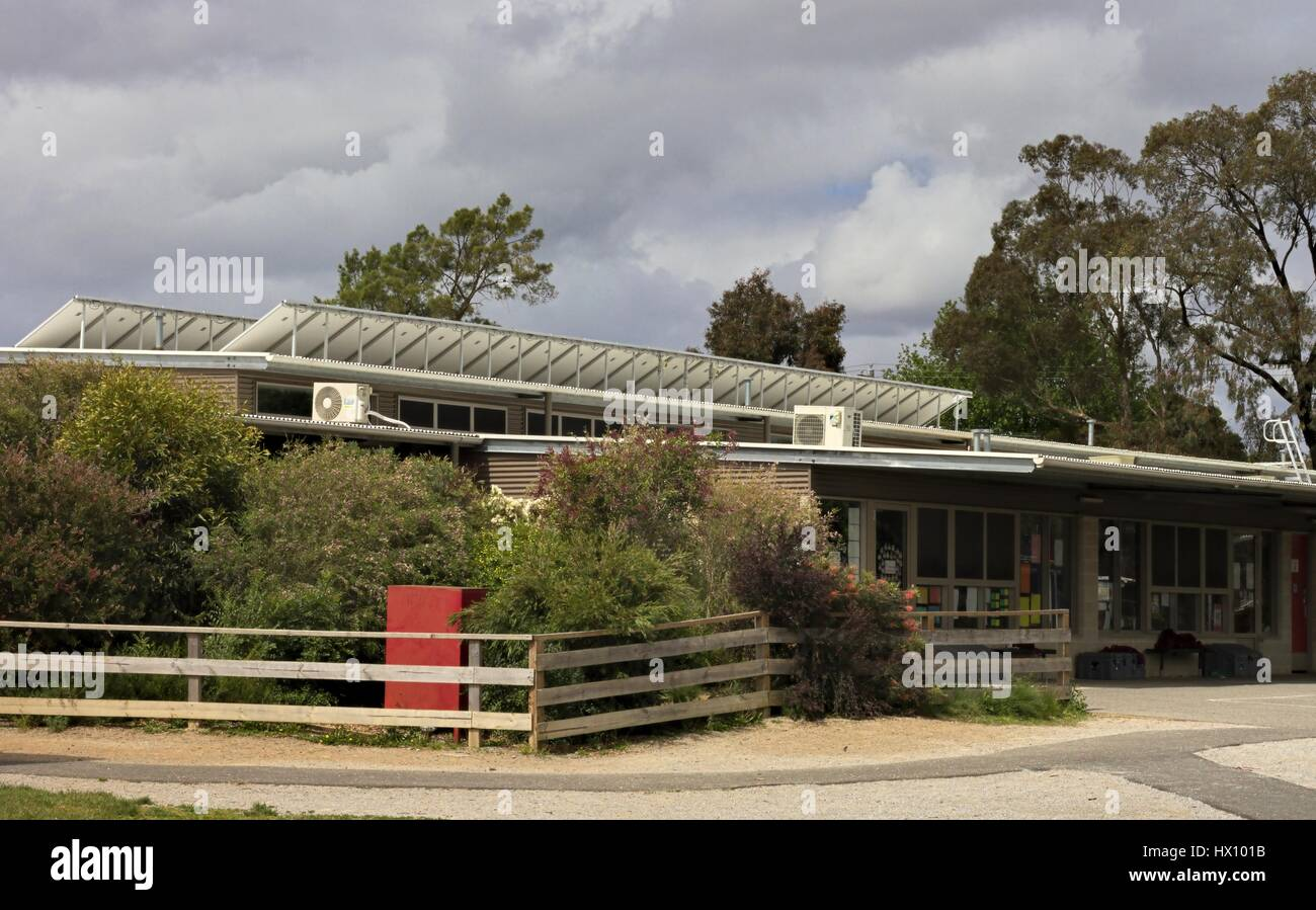 Reset Australian school classroom buildings with rows of solar panels raised to catch the sun. - Stock Image