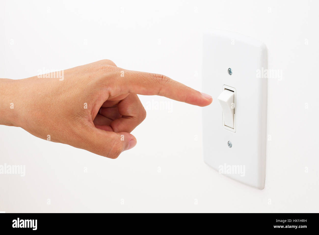 Hand turning light power switch on or off. - Stock Image