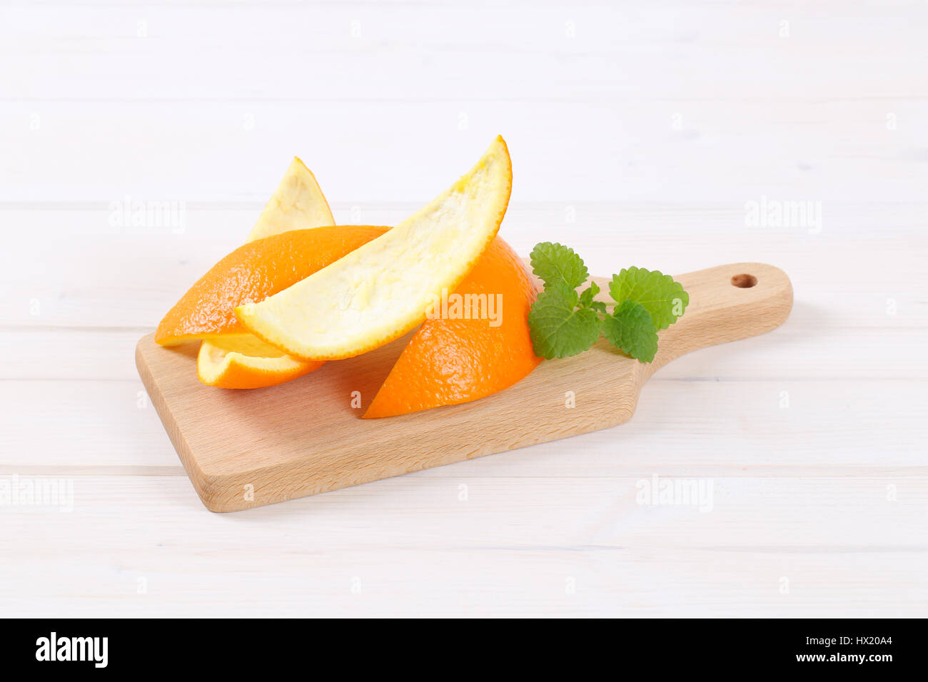 pile of orange peels on wooden cutting board - Stock Image