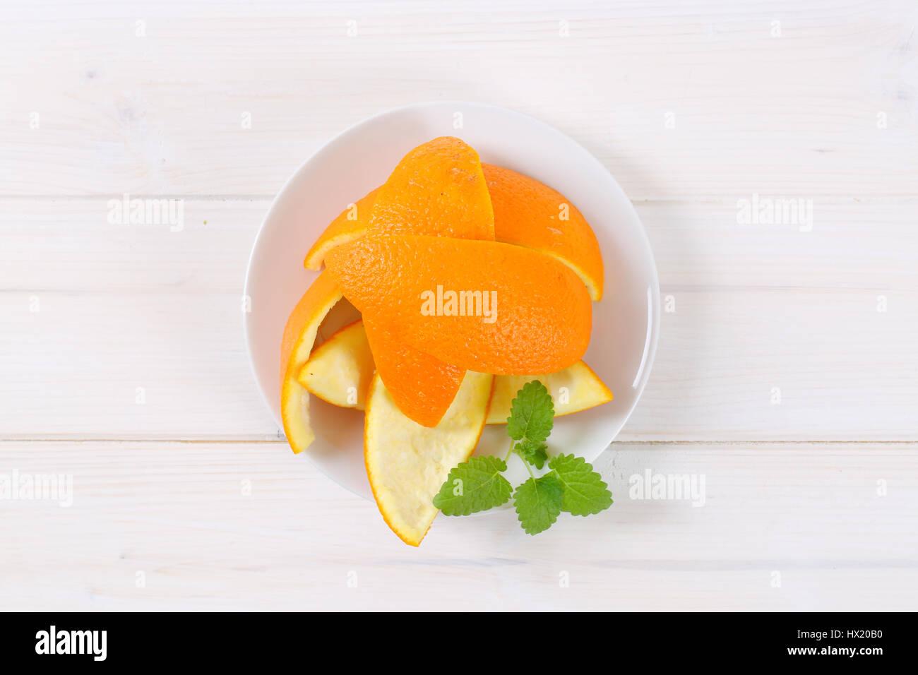 plate of orange peels on white background - Stock Image