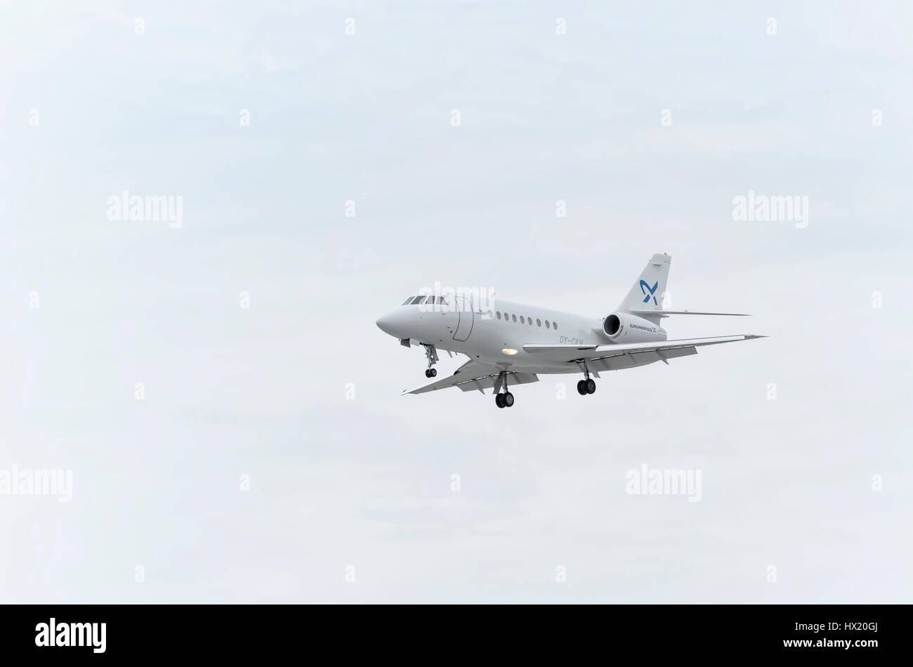 Business jet Dassault Falcon 2000, of Air Alsie charter airline, is landing on Madrid - Barajas, Adolfo Suarez airport. - Stock Image