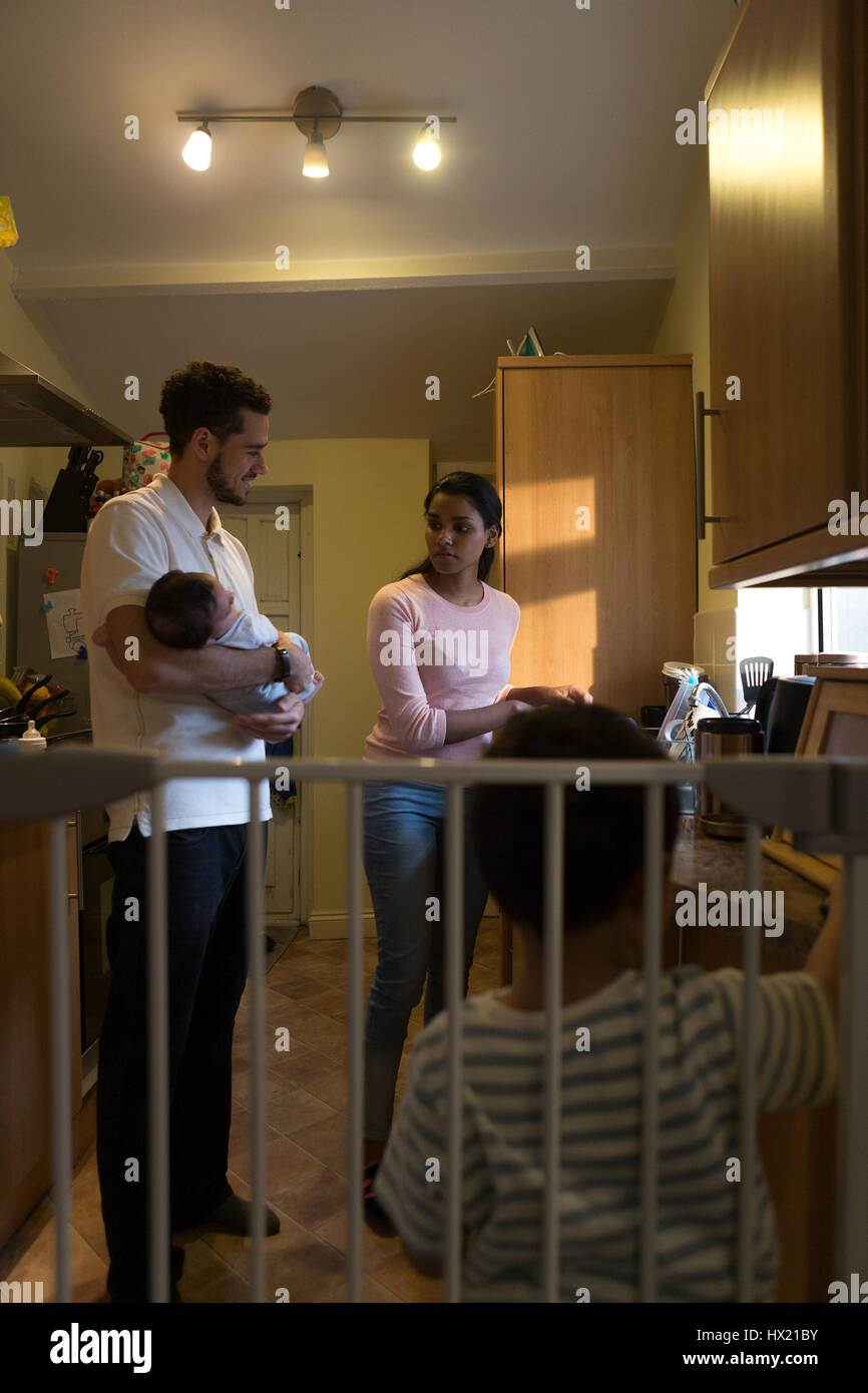 Young family in the kitchen. The mother is washing dishes and talking to her partner, who is holding their baby Stock Photo