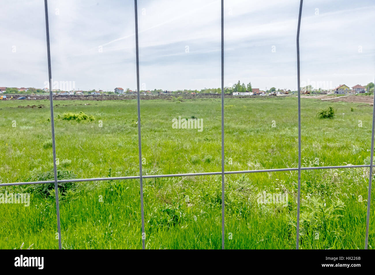 View on the construction site through a fence wire with quadratic shape. - Stock Image