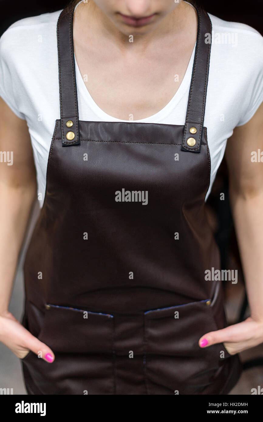 Young woman chef or waiter posing, wearing apron and t-shirt closeup - Stock Image