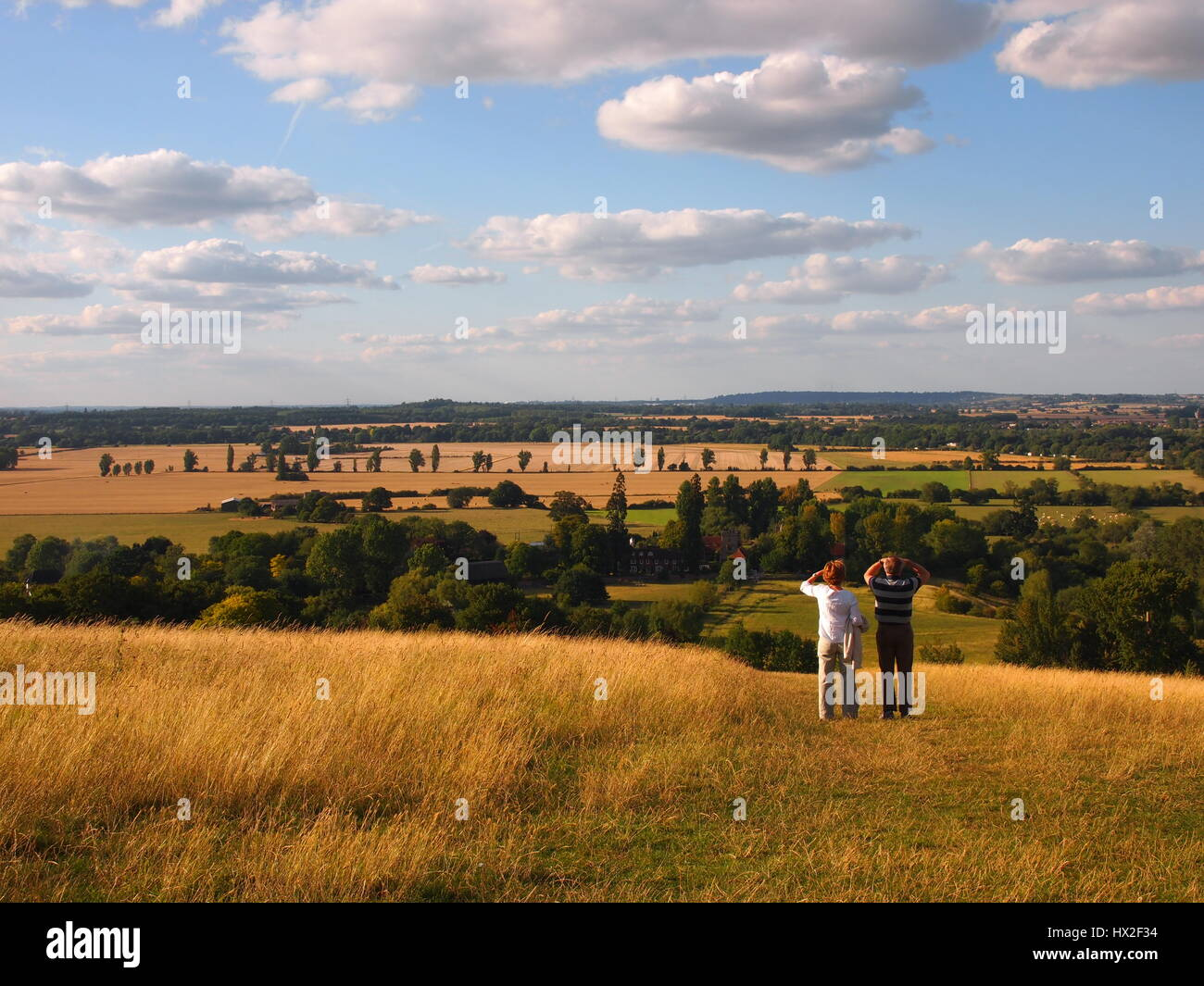 Two people enjoying the view from the top of Wittenham Clumps in Oxfordshire. Looking into the Thames Valley between - Stock Image