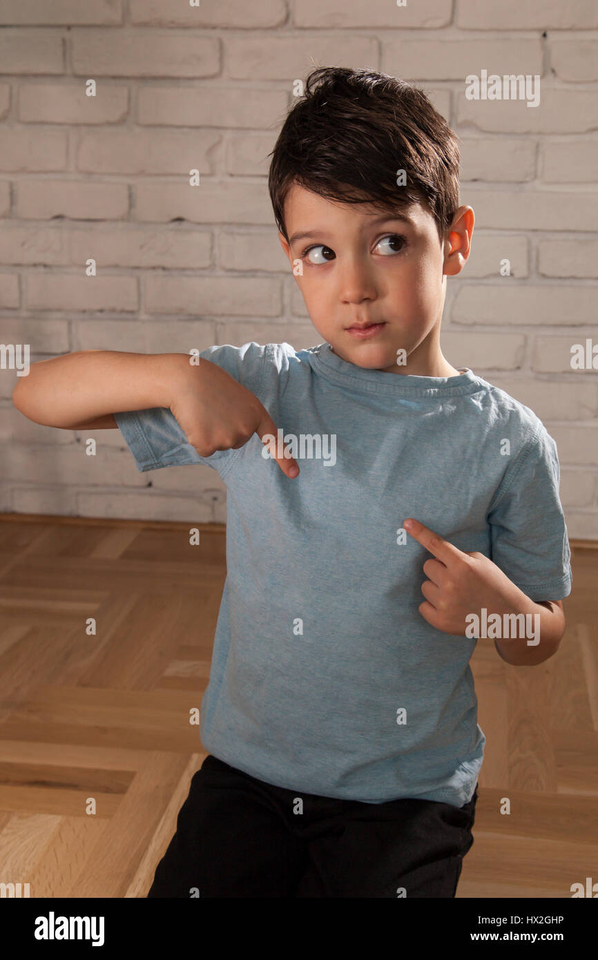 Happy boy pointing his fingers on a blank t-shirt - Stock Image