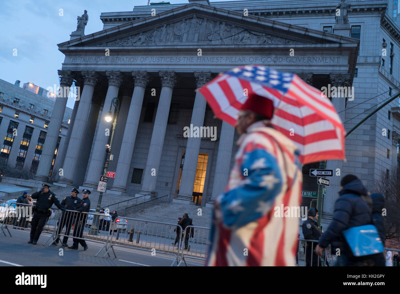Police look on from the barricaded steps of the New York Sate Supreme Court building. A protester dressed as a American - Stock Image